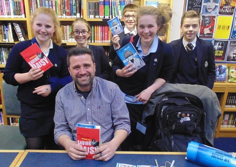 Phil Earle and students smiling holding his books at an speaking event